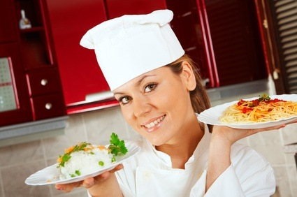 Closeup of young attractive female chef with dishes