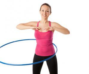 fitness woman dressed in pink top and black leggins working with hula hoop smiling isolated over white. Half lngth view
